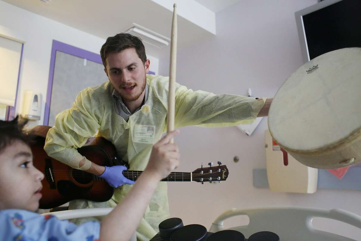 Jacobson plays and sings with 9-year-old Julian Barajas during a music therapy session.