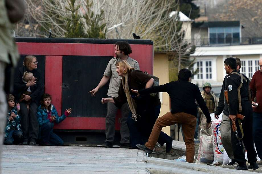 Foreigners are escorted by Afghan police after they were evacuated from a guesthouse during an attack by Taliban gunmen in Kabul on March 28, 2014.  Gunfire and explosions rocked Kabul as Taliban militants attacked a guesthouse used by foreigners, the latest violence to rock the Afghan capital just over a week before the presidential election. US-based aid group Roots for Peace, which works to replace minefields with vineyards, said Friday that its guesthouse was under attack in Kabul, and that at least three Afghans were wounded.   AFP PHOTO/WAKIL KOHSARWAKIL KOHSAR/AFP/Getty Images Photo: Wakil Kohsar, AFP/Getty Images