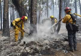 A fire crew from Stanislaus County douses a hot spot from the Rim Fire near Camp Mather on Friday, Aug. 23, 2013. Burning near Yosemite National Park, the wildfire has scorched over 150 square miles of terrain.