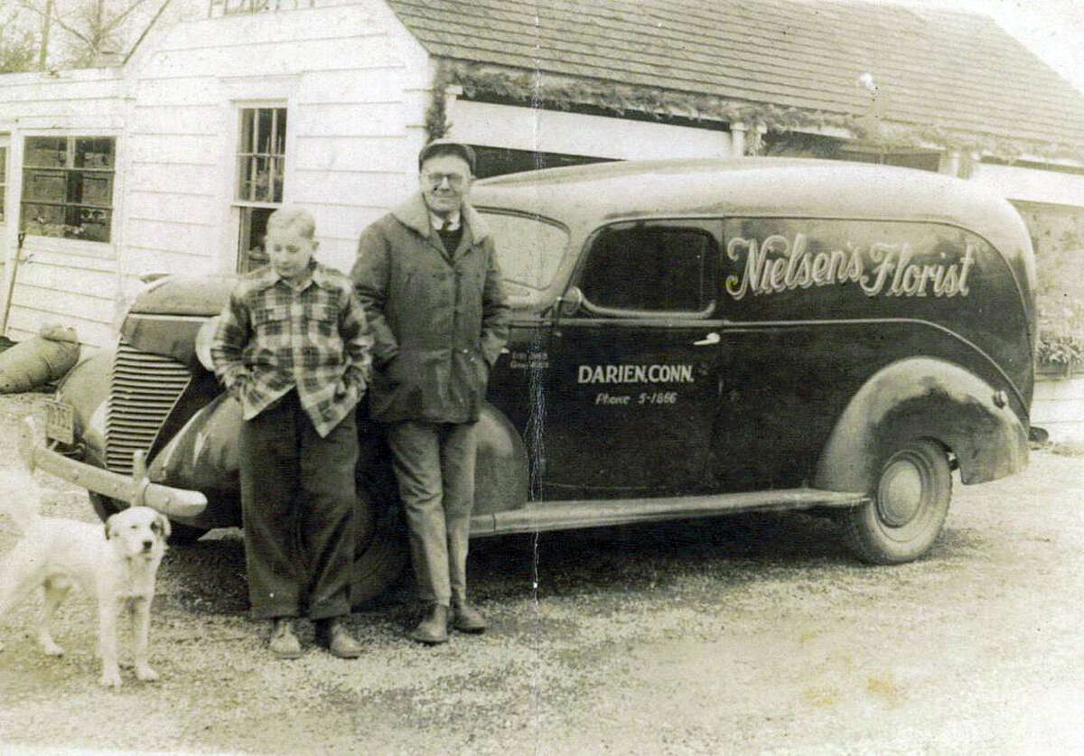 The first delivery car that Nielsen's Florist owned was a hearse purchased from Edward Lawrence Funeral Home. Picutred is Gerald and Christian Nielsen.