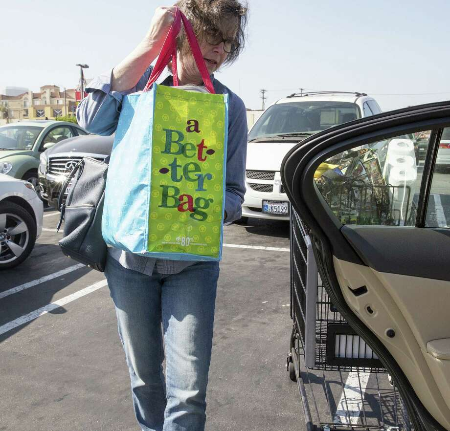 A shopper carries a reusable bag outside a grocery store in Los Angeles, where plastic bags are banned. San Antonio and Dallas may soon consider enacting similar bans. Austin enacted its ban last year. Photo: Monica Almeida / New York Times / NYTNS