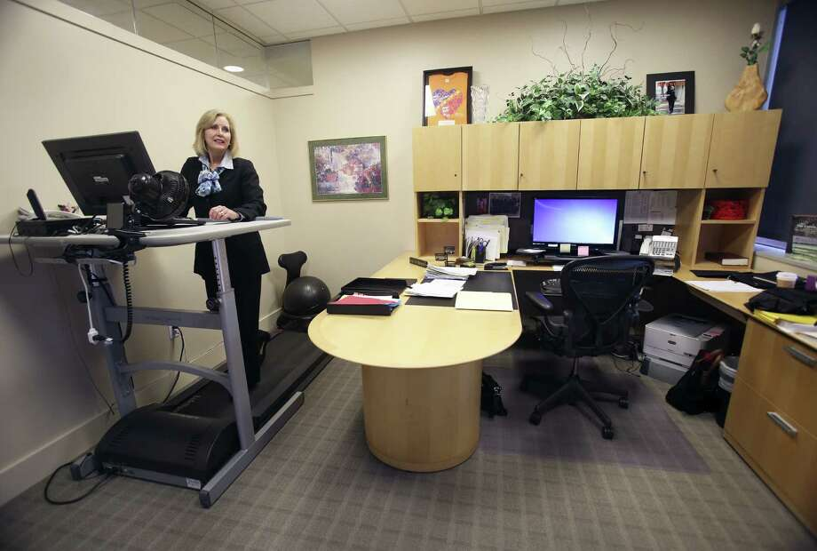 Mary DeLay, an executive at the UT Health Science Center at San Antonio, uses a treadmill desk in her office. She began using it to help with back pain but has found benefits of  more physical activity during the day, and it boosts her mood as well. Photo: Helen L. Montoya / San Antonio Express-News / SAN ANTONIO EXPRESS-NEWS