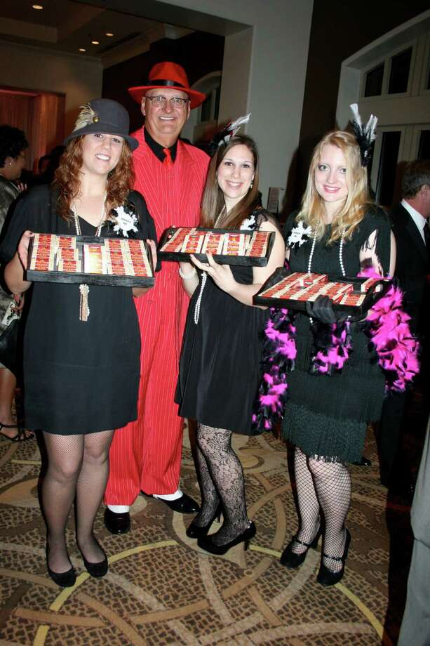 Dr. Dennis Halford, who attracted lots of attention in his red suit, posed with new Fort Bend ISD teachers, from left, Tara Cruse, Sarah Rodgers, and Rachel Geurlein.  The teachers were selling boxes of chalk - the way young women used to stroll through speak-easies with cigars and cigarettes -- to raise money for the New Teachers' Fund. Photo: Joan Vogan / For The Chronicle