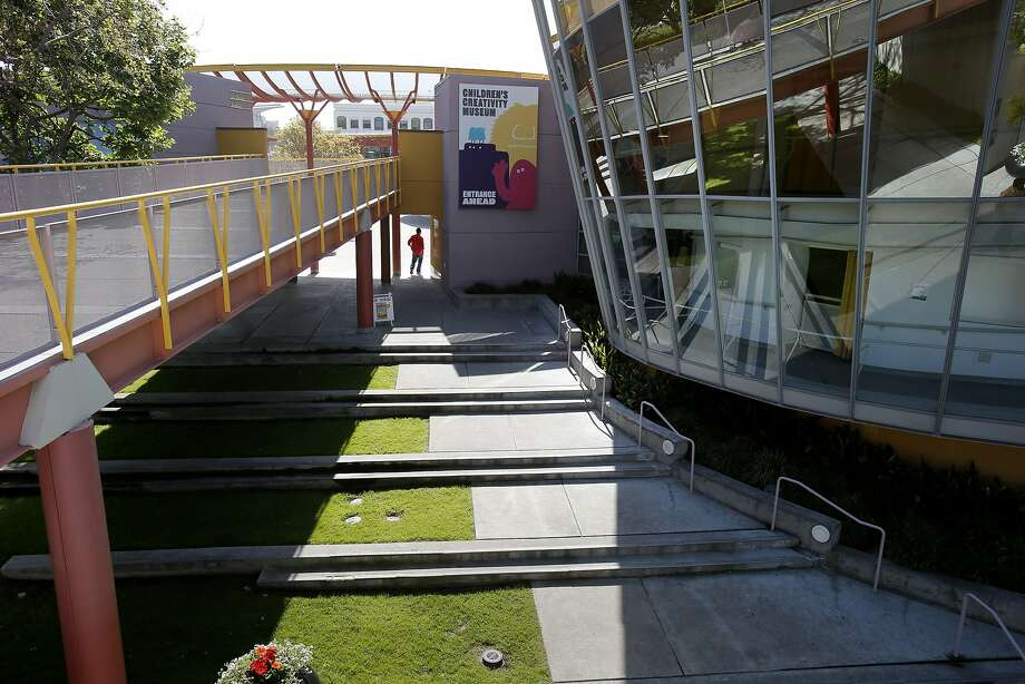 A walkway (left) connects to a pedestrian bridge, which would be replaced by a new one designed to touch down in terraced plazas between the carousel and the interior play areas. Photo: Brant Ward, The Chronicle