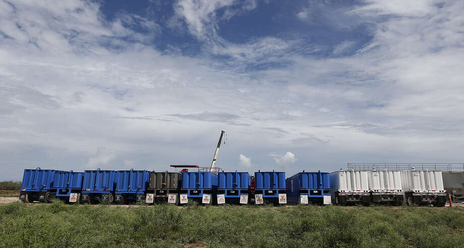 Storage tanks with fracturing material are lined up at a well on a ranch southwest of Ben Bolt. Drilling a well in the Eagle Ford shale also requires millions of gallons of water. Photo: Express-News File Photo / ©2013 San Antonio Express-News