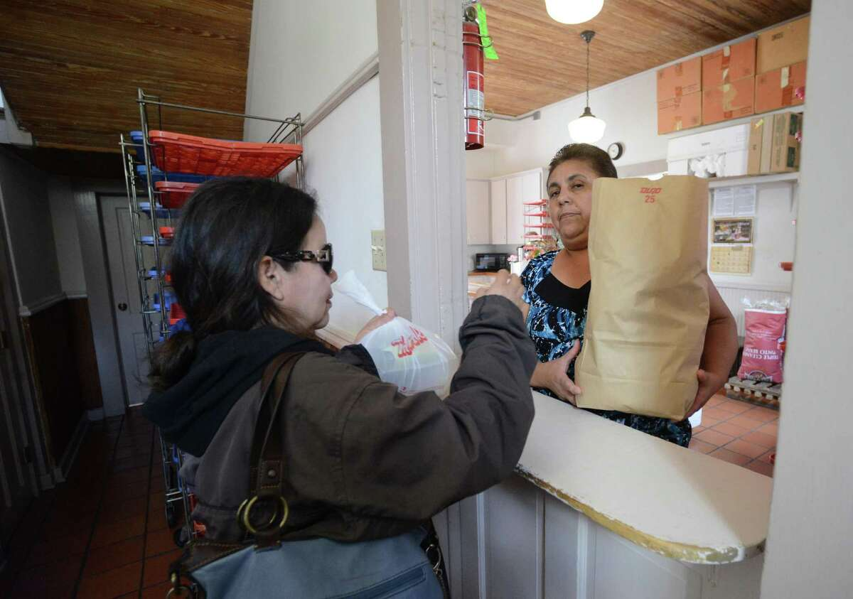 Martha Delgado, left, receives a bag of food items from Maria Torres a the The Little Church at La Villita food assistance program on Wednesday, March 19, 2014. The program is in danger of being shut down.