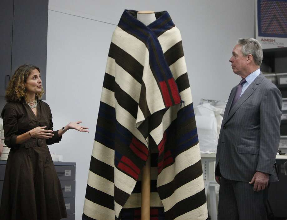 Jill d'Alessandro, curator of costume and textile arts at the Fine Arts Museums of San Francisco, discusses the donation of American Indian artifacts with Thomas Weisel. Photo: Lea Suzuki, The Chronicle