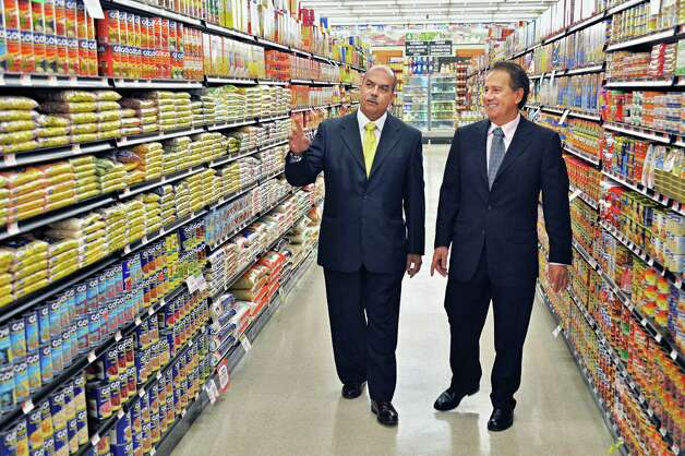 American Food Basket CEO Daniel Cabassa, left, and local store owner Frank Diaz tour the aisles of the Ideal Food Basket supermarket during their grand opening Friday, March 28, 2014, on Broadway in Menands, N.Y.  (John Carl D'Annibale / Times Union) Photo: John Carl D'Annibale / 00026306A