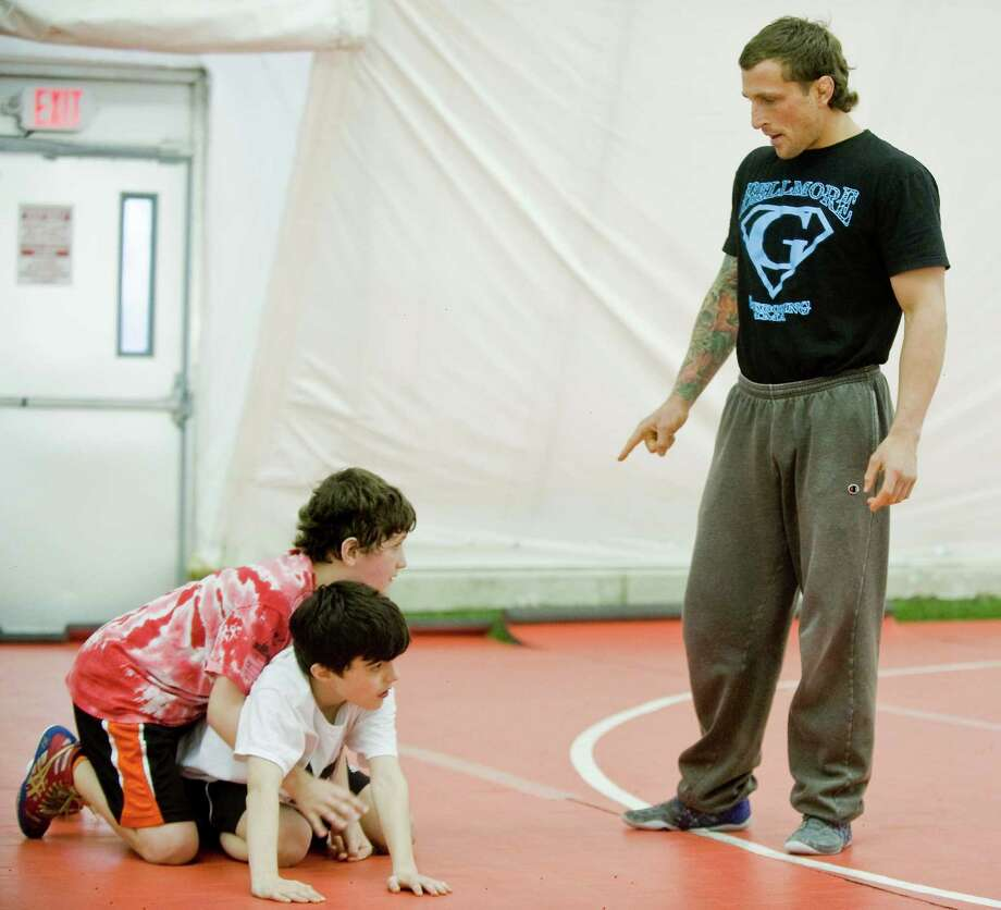 Devin Anderson, 11 on left, and Chris Bisignano,10, receive instruction from 2007 NCAA champion wrestler Gregor Gillespie during a wrestling clinic for The Beast Training Wrestling Club held at the Danbury Sports Dome. Friday, March 28, 2014 Photo: Scott Mullin / The News-Times Freelance