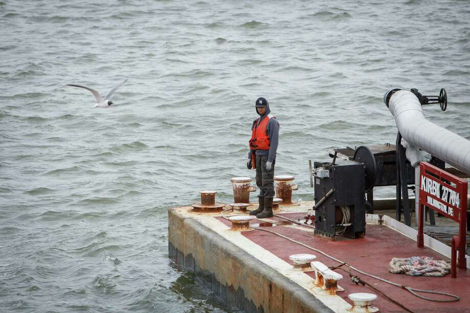 A deckhand prepares to park a loaded barge on the Houston Ship Channel, Wednesday, March 26, 2014.  Five people typically man the vessel as it transports a barge along the waterways.  ( Michael Paulsen / Houston Chronicle ) Photo: Michael Paulsen, Staff / © 2014 Houston Chronicle