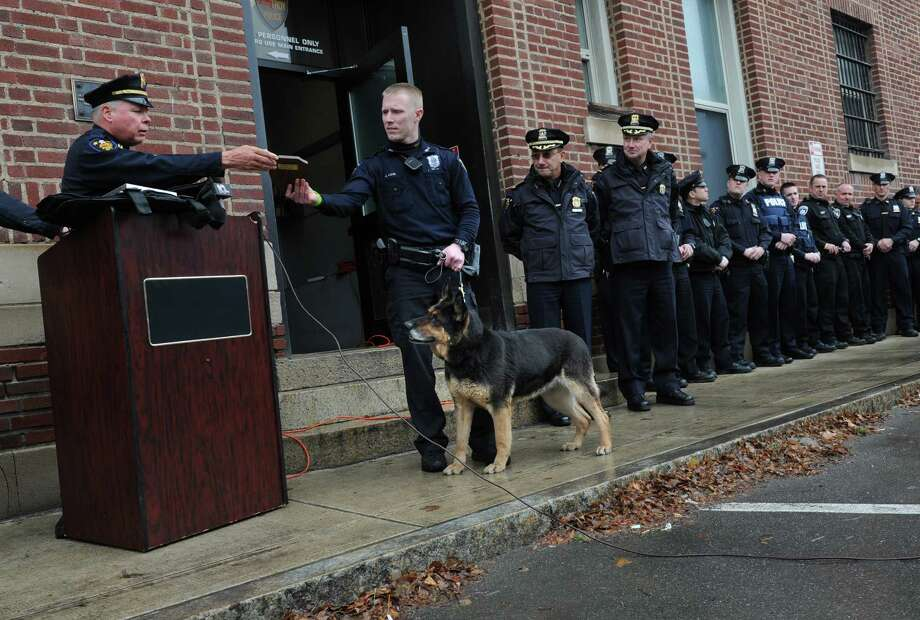 Capt. John Cooney, left, hands K-9 officer Justin Ashe a plaque for his partner K-9 officer Elza, as she gets a retirement sendoff from coworkers Friday, March 28, 2014, at the Troy Police Department in Troy, N.Y.  (Lori Van Buren / Times Union) Photo: Lori Van Buren / 00026296A
