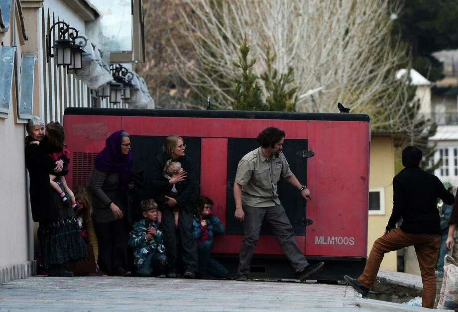 Foreigners take refuge behind a generator after they were evacuated from guesthouses during an attack by Taliban gunmen on Friday.  The gunmen apparently thought the site was being used to convert Muslims.. Photo: WAKIL KOHSAR, Stringer / AFP