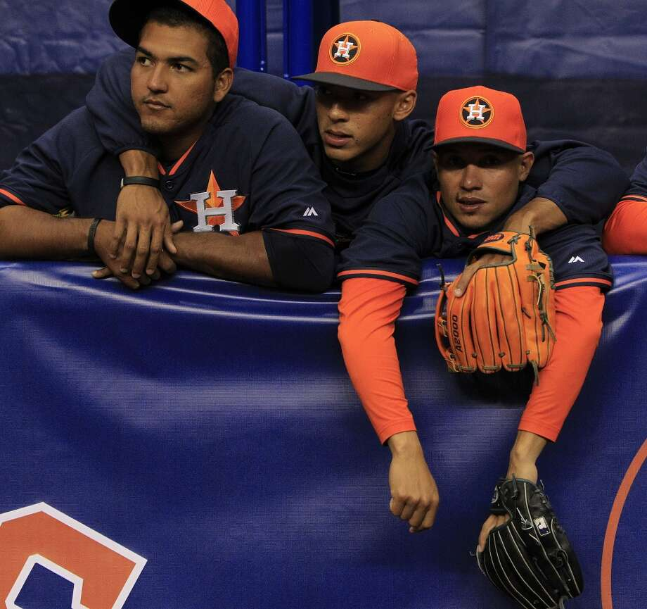 Astros catcher Carlos Perez, shortstop Carlos Correa and utility player Ronald Torreyes stand behind a fence during batting practice. Photo: Karen Warren, Houston Chronicle