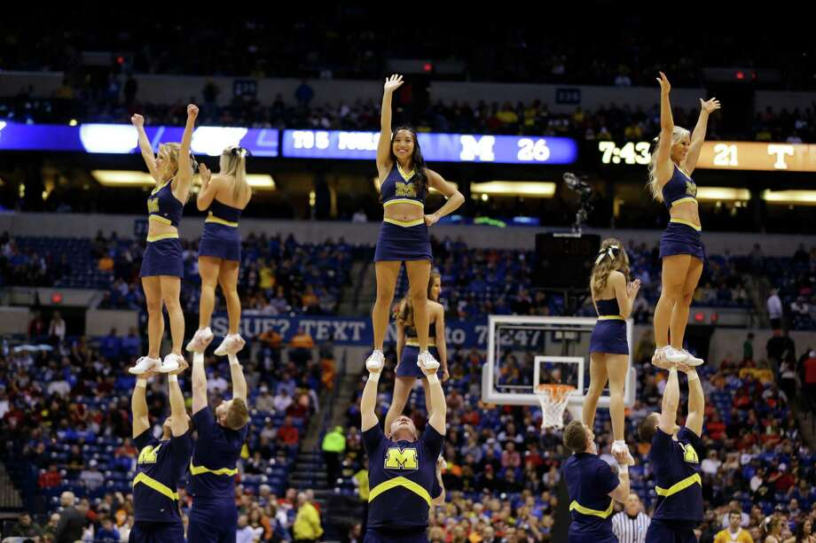Michigan cheerleaders perform during the first half of an NCAA Midwest Regional semifinal college basketball tournament game against the Tennessee Friday, March 28, 2014, in Indianapolis. (AP Photo/Michael Conroy) Photo: Michael Conroy, Associated Press / AP