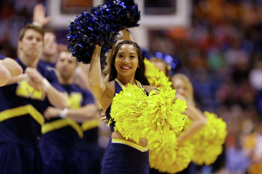 Michigan cheerleaders perform during the second half of an NCAA Midwest Regional semifinal college basketball tournament game against the Tennessee Friday, March 28, 2014, in Indianapolis. (AP Photo/Michael Conroy) Photo: Michael Conroy, Associated Press / AP