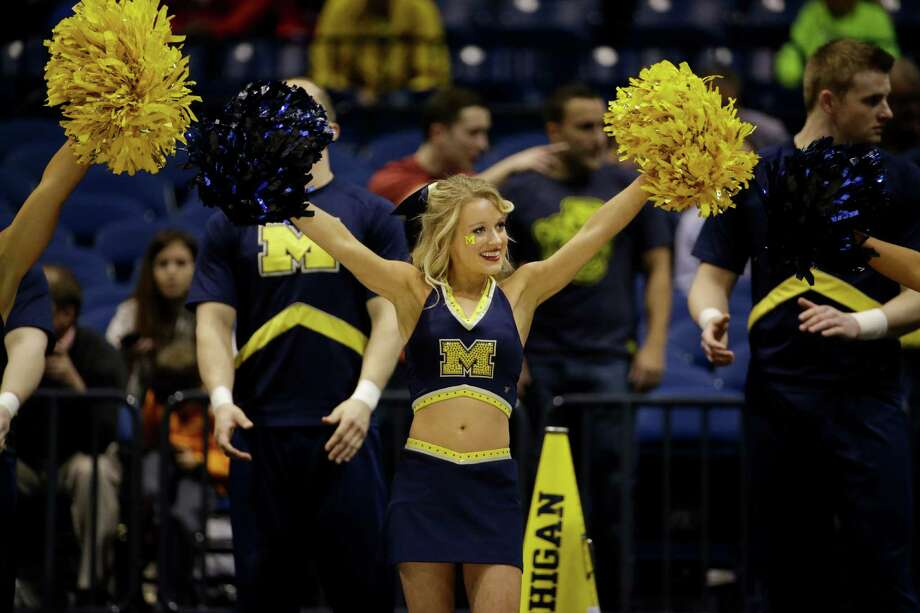 Michigan cheerleaders perform before an NCAA Midwest Regional semifinal college basketball tournament game between the Michigan and the Tennessee Friday, March 28, 2014, in Indianapolis. (AP Photo/David J. Phillip) Photo: David J. Phillip, Associated Press / AP