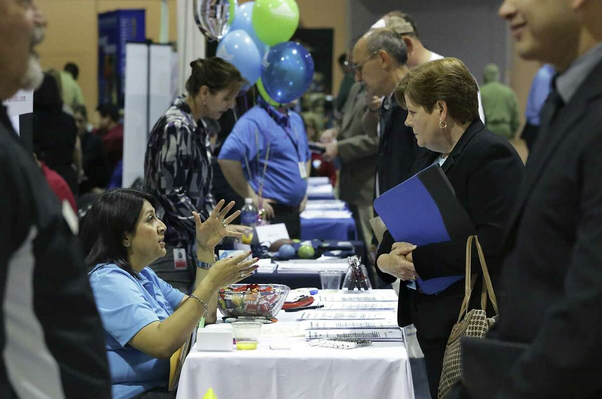 Jennifer Soto of DPT Laboratories talks with Denise Craigen, a military wife, during the job fair.