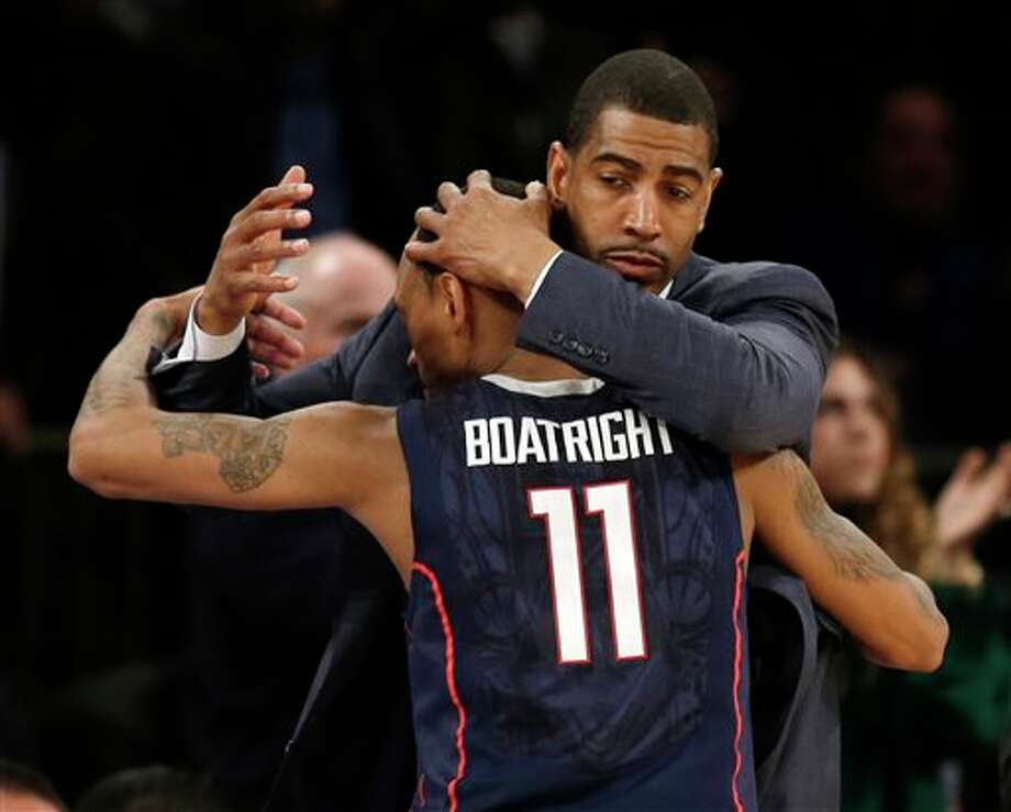 Connecticut coach Kevin Ollie  hugs Ryan Boatright.