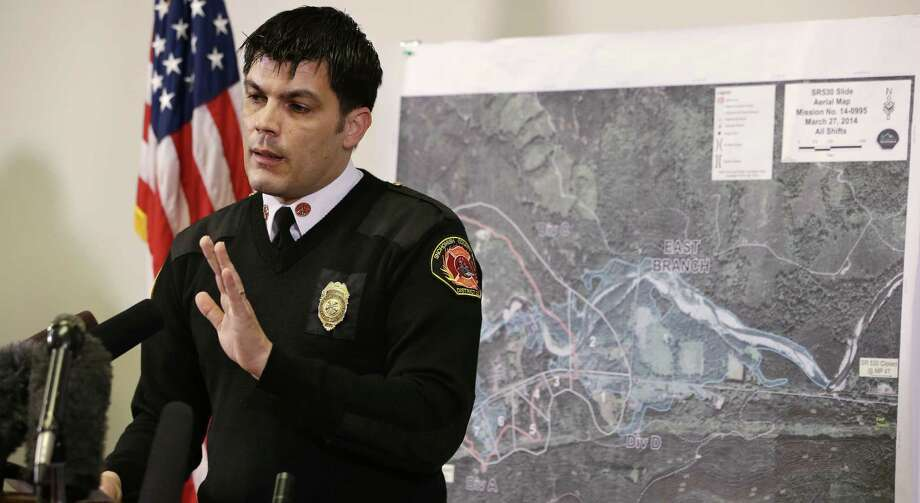 With a map of the deadly mudslide behind him, Snohomish County District 21 Fire Chief Travis Hots addresses a news conference about the search in Oso, Wash. The official death toll Friday was 17. Photo: Elaine Thompson / Associated Press / AP