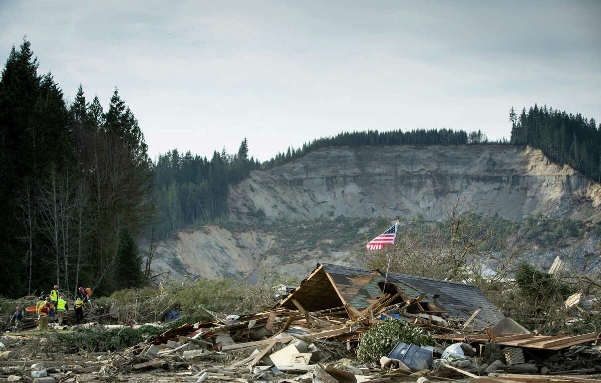 Rescue workers, left, remove a body from the debris field of the Oso mudslide.