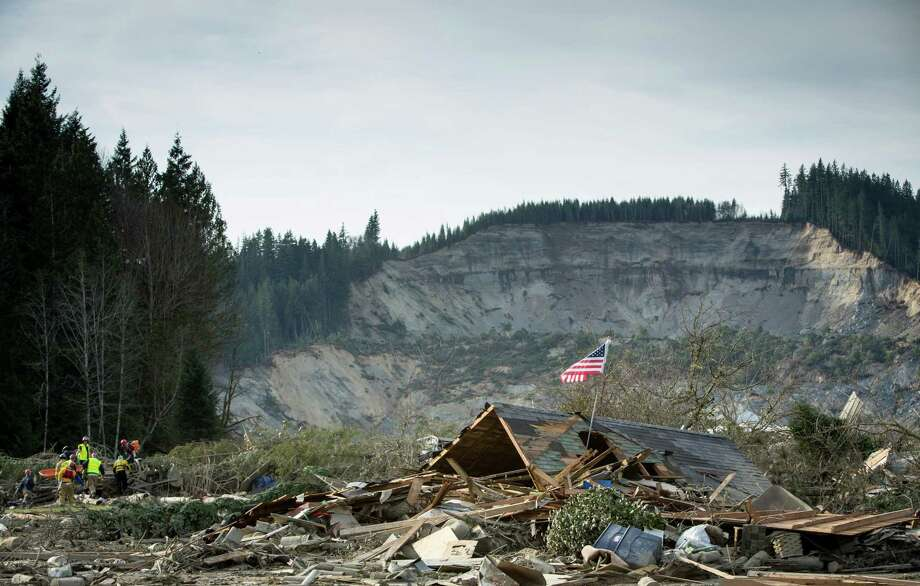 Rescue workers, left, remove a body from the debris field of the Oso mudslide. Photo: JOSHUA TRUJILLO, SEATTLEPI.COM / SEATTLEPI.COM