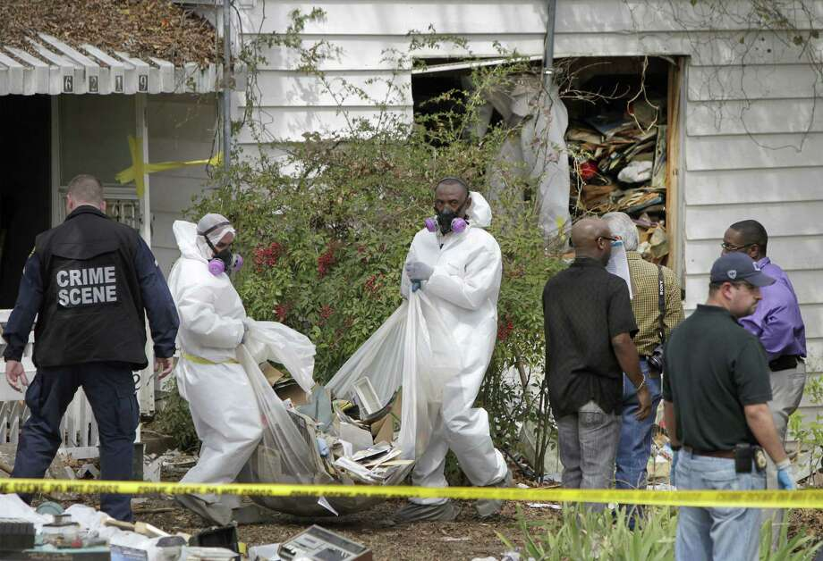 Hazardous materials contractors for the city remove debris from the home where the body of the homeowner was found in Dallas. Photo: Associated Press / The Dallas Morning News