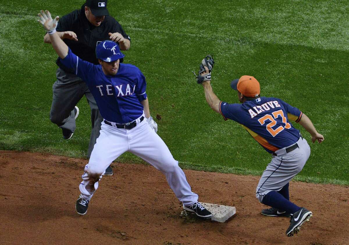 Donnie Murphy (16) of the Texas Rangers is safe at second as Jose Altuve (27) of the Houston Astros applies a late tag during Big League Weekend baseball action in the Alamodome on Friday, March 28, 2014.