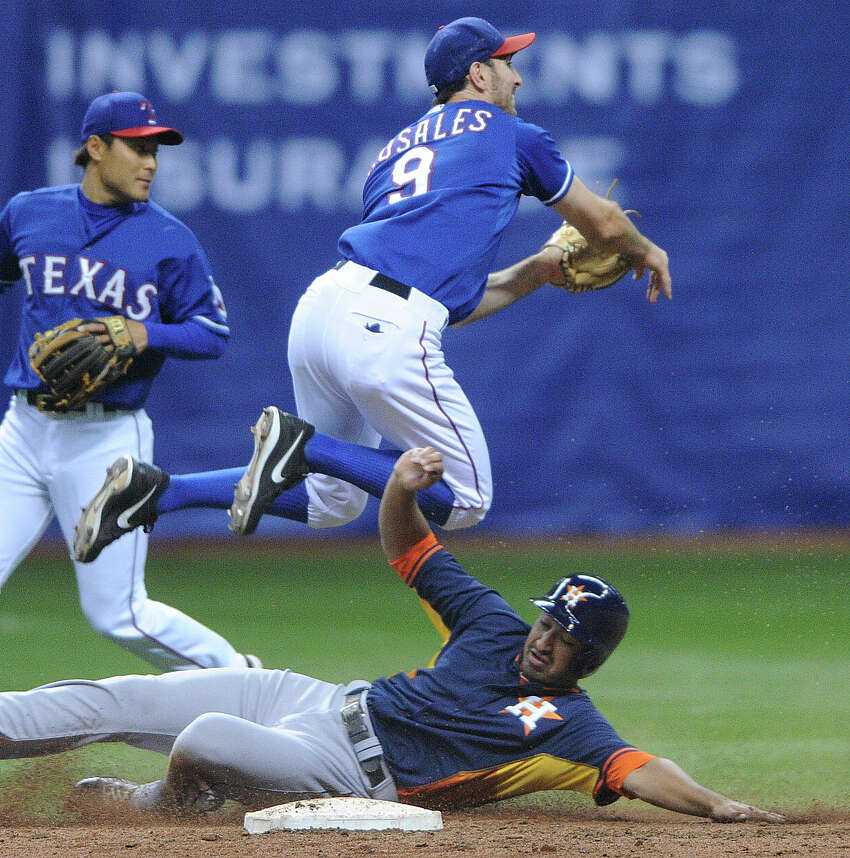 Adam Rosales (9) of the Texas Rangers turns a double play as Jesus Guzman of the Houston Astros slide in during Big League Weekend baseball action in the Alamodome on Friday, March 28, 2014.