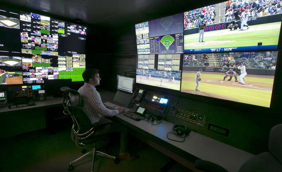 A technician works in front of a bank of TV screens at Major League Baseball's Replay Operations Center in New York. Photo: Richard Drew, Associated Press