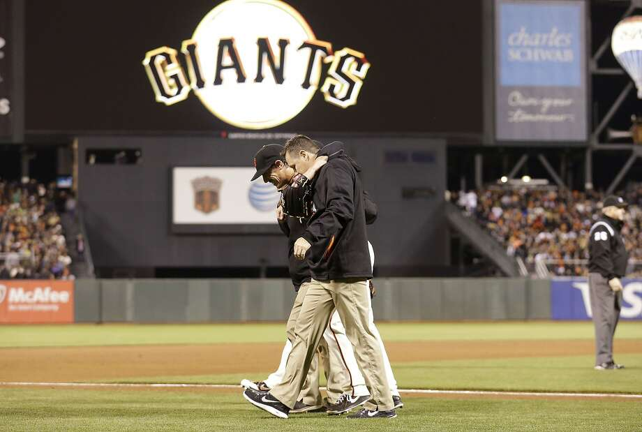 Pitcher Tim Lincecum is helped off the field by trainers after being nailed on the left knee by Daric Barton's liner in the fourth inning. Photo: Jeff Chiu, Associated Press