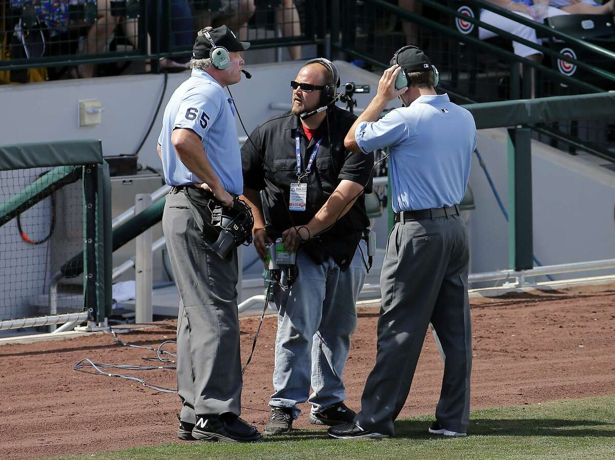 Umpires Ted Barrett (65) and Todd Tichenor, right, listen to the instant replay booth to decide whether a double hit by Los Angeles Angels Josh Hamilton was a home run, against the Chicago Cubs during the third inning of a spring training baseball game, Tuesday, March 25, 2014, in Mesa, Ariz. The hit was ruled a double after replay. (AP Photo/Matt York)