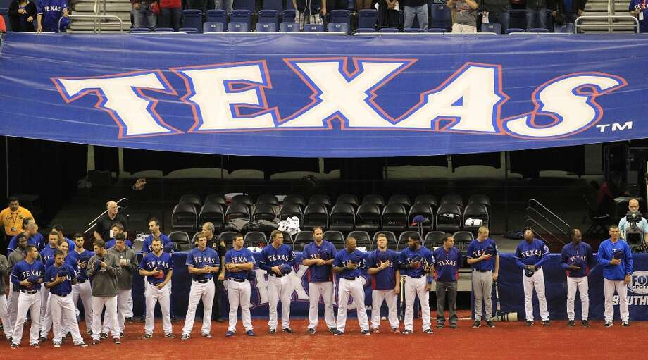 The Rangers stand outside of their dugout. Photo: Karen Warren, Houston Chronicle