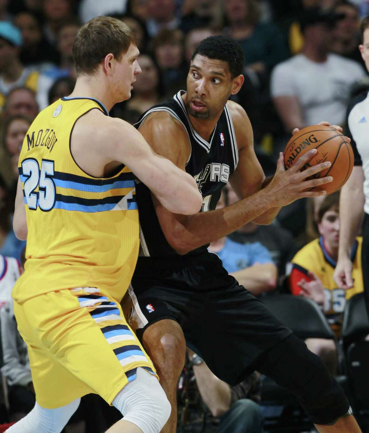 Tim Duncan (right) works the ball inside as the Nuggets' Timofey Mozgov defends. Duncan finished with 20 points, eight rebounds and two blocks.
