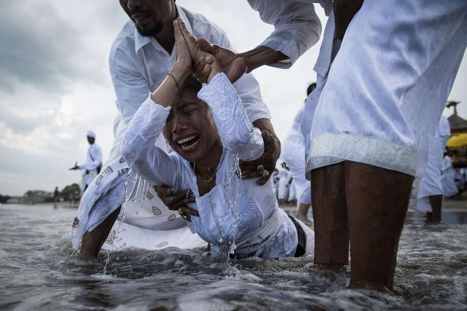BADUNG, BALI, INDONESIA - MARCH 28:  A Balinese woman cries while in a state of trance during Melasti Ceremony at a beach on March 28, 2014 in Badung, Bali, Indonesia.The Melasti ritual is held annually ahead of the Nyepi Day of Silence, a ceremony intended to cleanse and purify the souls of the Balinese Hindu participants. Nyepi is a Hindu celebration observed every new year according to the Balinese calendar. The national holiday is one of self-reflection and meditation and activities such as working, watching television or travelling are restricted between the hours of 6 a.m. and 6 p.m.  (Photo by Agung Parameswara/Getty Images) *** BESTPIX *** Photo: Agung Parameswara, Getty Images