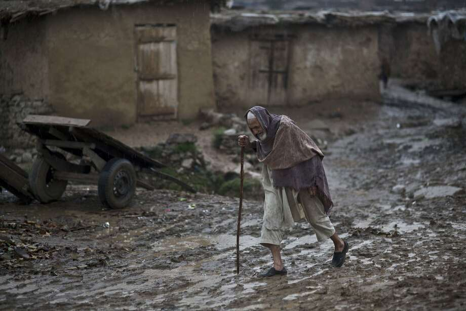 An elderly Afghan refugee man walks toward the main road through a muddy slippery track, during a rainfall in a poor neighborhood on the outskirts of Islamabad, Pakistan, Friday, March 28, 2014. For more than three decades, Pakistan has been home to one of the world's largest refugee communities: hundreds of thousands of Afghans who have fled the repeated wars and fighting in their country. Since the 2002 U.S.-led invasion of Afghanistan some 3.8 million Afghans have returned to their home country, according to the U.N.'s refugee agency, thousands of them still live without electricity, running water and other basic services. (AP Photo/Muhammed Muheisen) Photo: Muhammed Muheisen, Associated Press