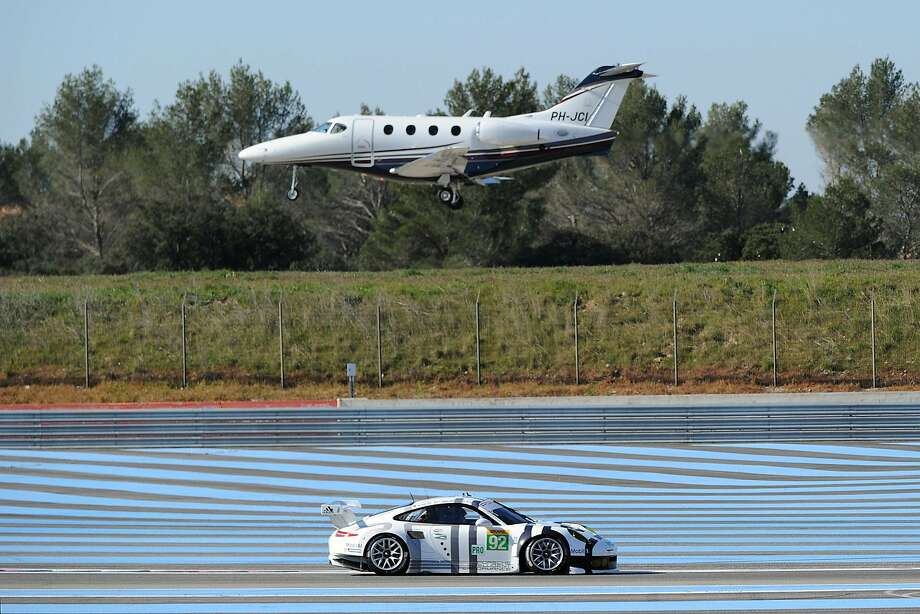 TOPSHOTS The Porshe 911 RSR driven by Marco Holzer (DEU) Frederic Makowiecki (FRA) and Richard Lietz (AUT) is seen while a plane flies over on March 28, 2014 during the first day of the WEC training session in Le Castellet, southern France. AFP PHOTO / BORIS HORVATBORIS HORVAT/AFP/Getty Images Photo: Boris Horvat, AFP/Getty Images