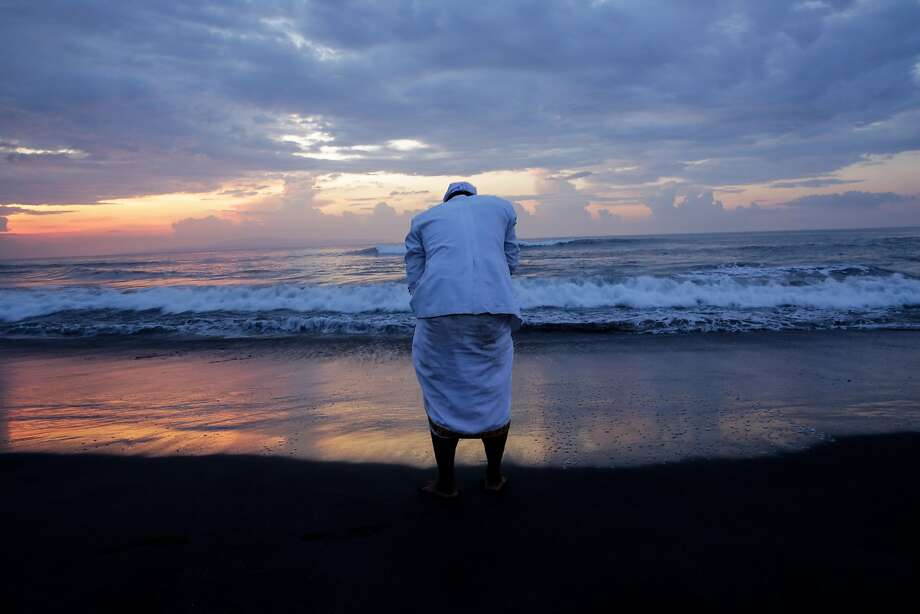 GIANYAR, INDONESIA - MARCH 28:  A Balinese man takes seawater during Melasti Ceremony at Purnama Beach on March 28, 2014 in Gianyar, Bali, Indonesia.The Melasti ritual is held annually ahead of the Nyepi Day of Silence, a ceremony intended to cleanse and purify the souls of the Balinese Hindu participants. Nyepi is a Hindu celebration observed every new year according to the Balinese calendar. The national holiday is one of self-reflection and meditation and activities such as working, watching television or travelling are restricted between the hours of 6 a.m. and 6 p.m.  (Photo by Agung Parameswara/Getty Images) ***BESTPIX*** Photo: Agung Parameswara, Getty Images