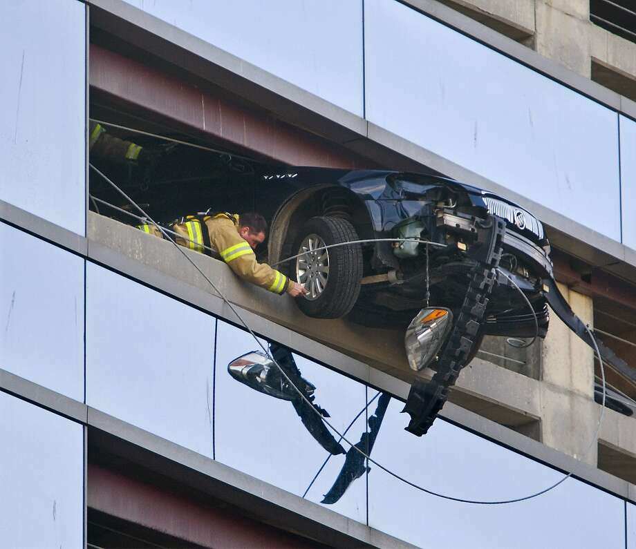 "A firefighter secures a cable to the wheel of a car that went through the retaining wall on the seventh floor of the Damon West Parking Ramp in downtown Rochester, Minn. on Friday morning, March 28, 2014. The driver was uninjured and firefighters were eventually able to pull the car back through the retaining wall. The woman driving the vehicle told authorities she had stepped on the brake as she pulled in to park, but the car ""still surged forward,"" said Mike Bjoraker, assistant fire marshal. (AP Photo/The Rochester Post-Bulletin, Jerry Olson) Photo: Jerry Olson, Associated Press"