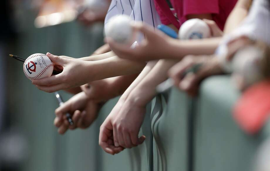 Fans hold baseballs for autographs before an exhibition baseball game between the Minnesota Twins and the Boston Red Sox in Fort Myers, Fla., Friday, March 28, 2014. (AP Photo/Gerald Herbert) Photo: Gerald Herbert, Associated Press