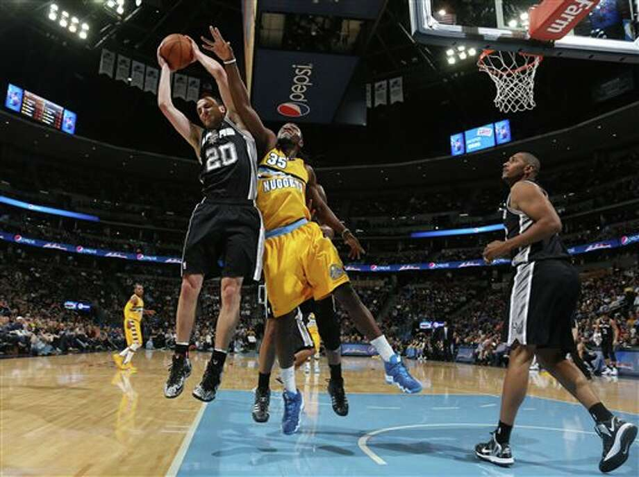 From left, San Antonio Spurs guard Manu Ginobili (20), of Argentina, pulls in a rebound in front of Denver Nuggets forwards Kenneth Faried and Boris Diaw, of France, in the first quarter of an NBA basketball game in Denver, Friday, March 28, 2014. (AP Photo/David Zalubowski) Photo: David Zalubowski, AP / AP