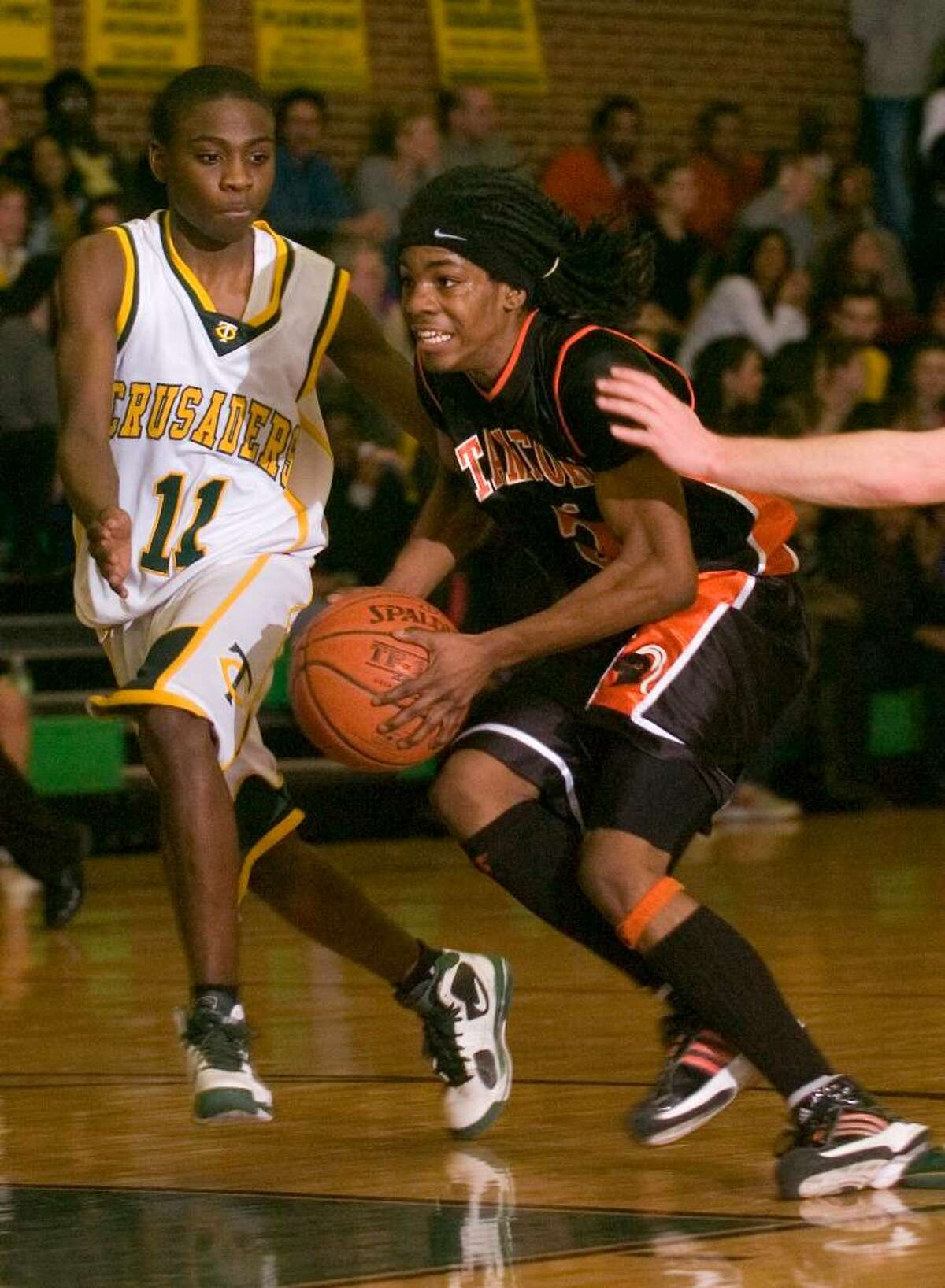 Stamford's Jakai Wilson, right, tries to get around Trinity's Schadrac Casimir, left, during an FCIAC boys basketball game at Trinity Catholic High School in Stamford, Conn. on Tuesday, Feb. 9, 2010.