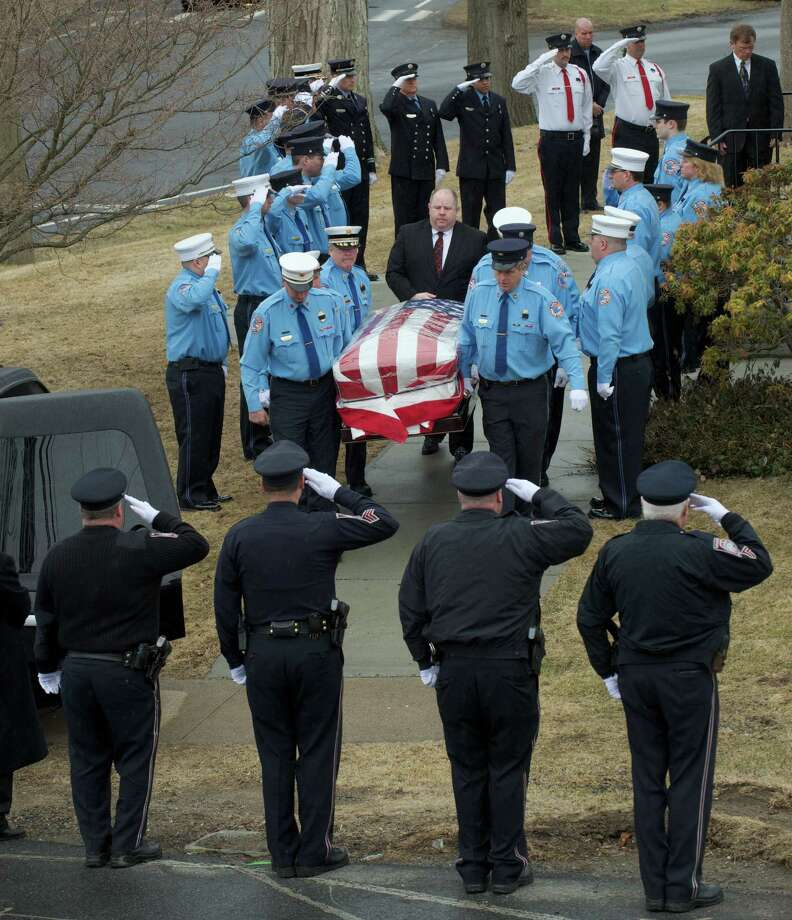 Pallbearers carry the casket of Lou Rell, husband of former Connecticut Governor M. Jody Rell, of Brookfield, Conn, out of the Congregational Church of Brookfield, on Saturday, March 29, 2014, following his funeral service. An honor guard containing members of the Brookfield Volunteer Fire Company, Brookfield Volunteer Fire Department Candlewood Company and Brookfield Police Department stands at attention as it passes. Photo: H John Voorhees III / The News-Times Freelance