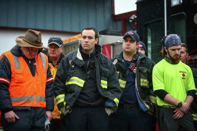 Rescue workers and volunteers outside the Darrington Fire Department pause during a state-wide moment of silence to honor the victims of the Oso mud slide one week earlier. Photographed on Saturday, March 29, 2014. Photo: JOSHUA TRUJILLO, SEATTLEPI.COM / SEATTLEPI.COM