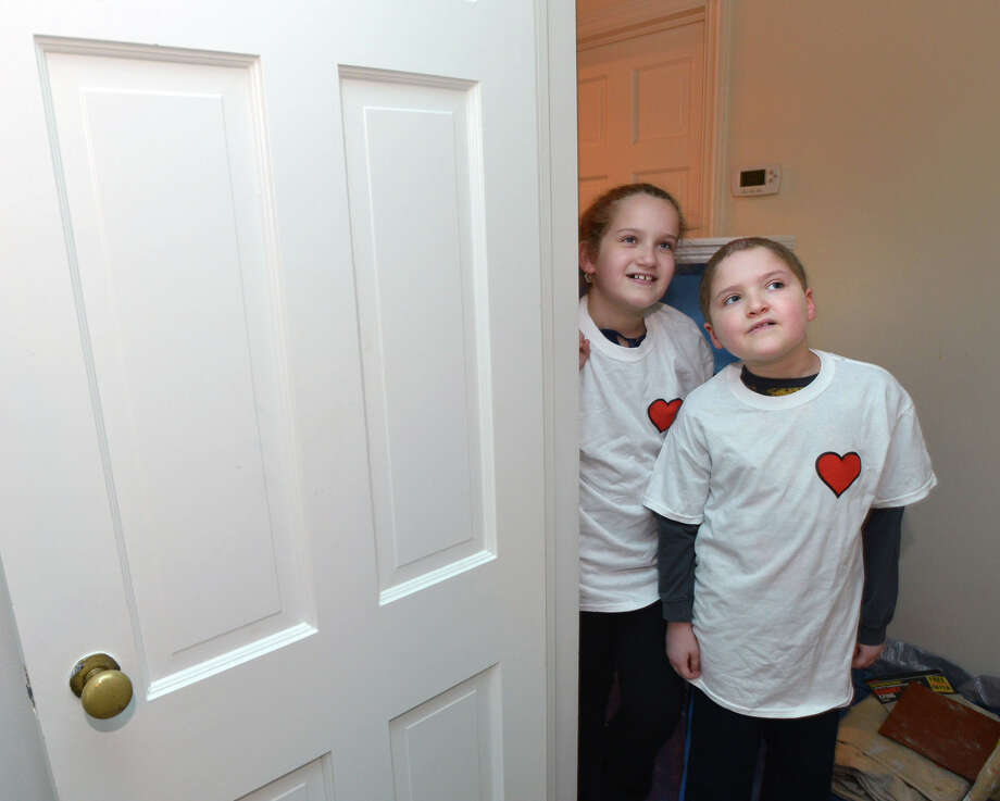 At right, Zach Libow, 7, who is battling leukemia, and his sister, Jordyn, 10, look on as Art from the Heart volunteers use paint to transform Zach's bedroom into an undersea world at his Riverside home, Saturday, March 29, 2014. The Art from the Heart volunteers are a part of the program of Circle of Care for Families of Children with Cancer, which does room makeovers for young cancer patients throughout southern Connecticut and northern Westchester County. Photo: Bob Luckey / Greenwich Time