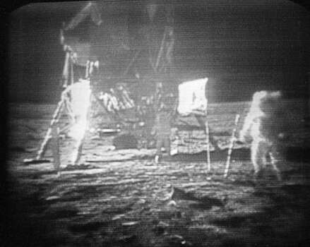 In this July 20, 1969 file photo, Apollo 11 astronaut Neil Armstrong, right, trudges across the surface of the moon leaving behind footprints.  The U.S. flag, planted on the surface by the astronauts, can be seen between Armstrong and the lunar module.  Edwin E. Aldrin is seen closer to the craft.  The men reported the surface of the moon was like soft sand and they left footprints several inches deep wherever they  walked. Photo: AP