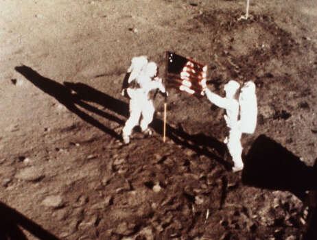 Apollo 11 astronauts Neil Armstrong and Edwin E. 'Buzz' Aldrin, the first men to land on the moon, plant the U.S. flag on the lunar surface, July 20, 1969.  Photo was made by a 16mm movie camera inside the lunar module, shooting at one frame per second. Photo: AP