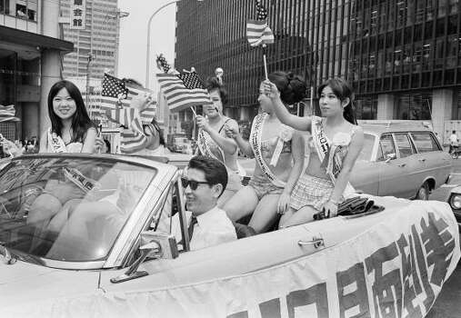 "Bikini clad hostesses of a Tokyo cabaret, led by their manager, shout ""Banzai"" cheers in Japanese, in front of the U.S. Embassy, July, 1969, Tokyo Japan. They were celebrating the successful landing of the Apollo 11 lunar module on the moon. The girls carry signs reading ""Congratulation for successful landing on the Moon."" Photo: ASSOCIATED PRESS"
