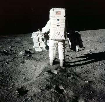 Edwin Buzz Aldrin carries scientific experiments to a deployment site south of the lunar module Eagle. One experiment involved the inner composition of the moon, and another tried to determine the exact distance from Earth. Photo was taken by Neil Armstrong of the Apollo 11 mission in July 1969. From the book  Full Moon (Knopf) by Michael Light. Photo: AP