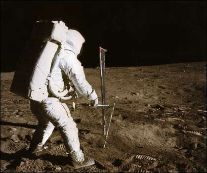 "Picture taken by US astronaut Neil Armstrong of astronaut Edwin ""Buzz"" Aldrin conducting an experiment on the moon's surface on July 20, 1969, during the Apollo XI space mission. As an estimated 500 million people around the world waited with bated breath crowded around fuzzy television screens and radios, Armstrong stepped down the lunar module's ladder and onto the lunar surface on July 20, 1969. ""That's one small step for man, one giant leap for mankind,"" Armstrong intoned, his words slightly distorted by distance and communications equipment, in a phrase now etched forever into the history books. Photo: -, AFP/Getty Images"