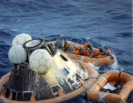 "US Navy pararescueman Lieutenant Clancey Hatleberg disinfects Apollo 11 astronauts Neil Armstrong, Michael Collins, and Edwin ""Buzz"" Aldrin in a life raft during recovery operations on July 24, 1969 at the successful completion of their lunar landing mission. Photo: -, AFP/Getty Images"